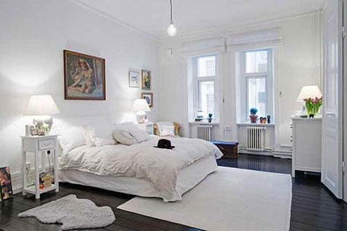 Donkerebruine vloer in witte slaapkamer