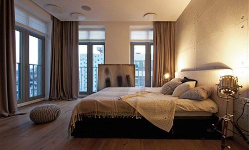 Betonnen muren en houten vloer in slaapkamer