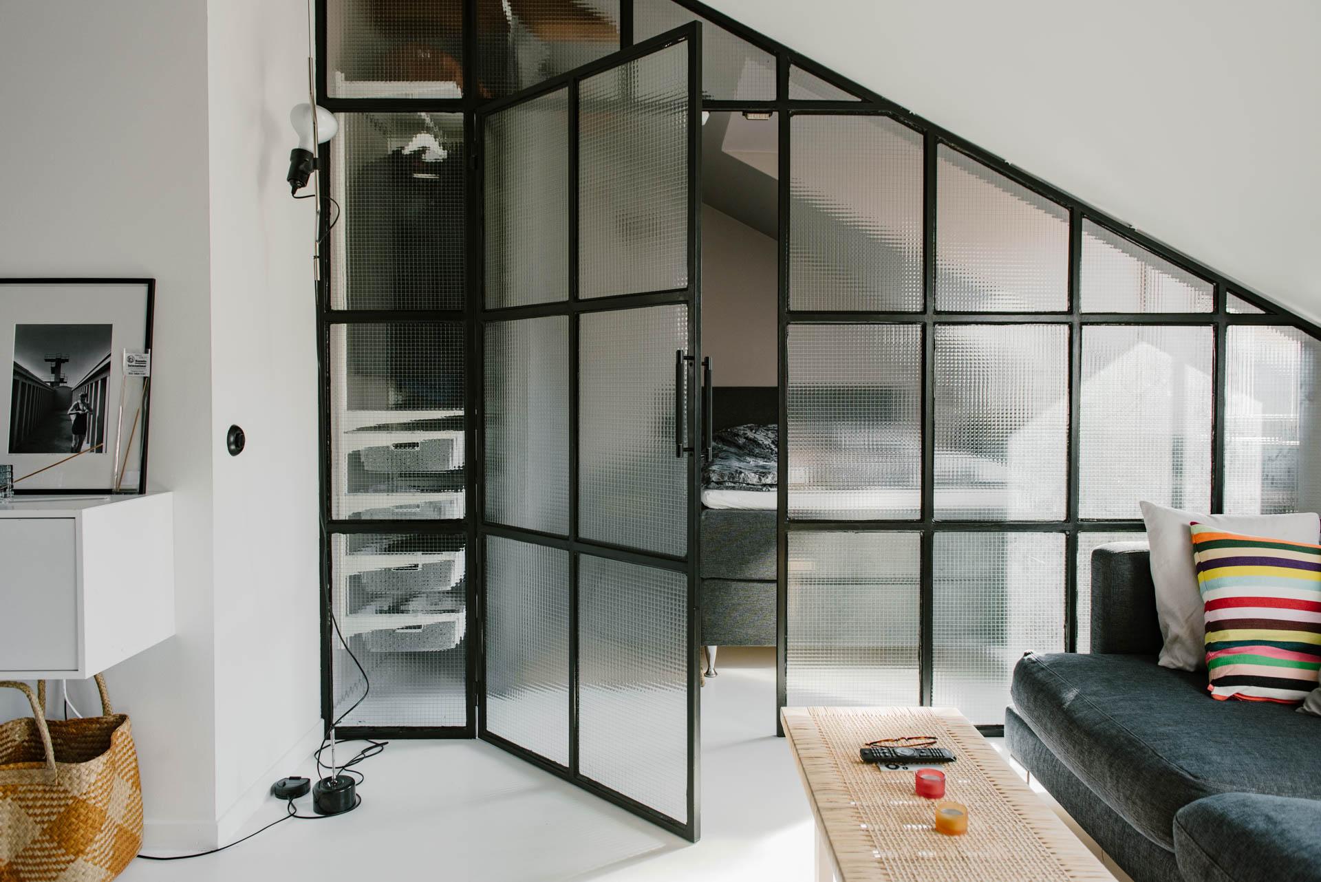 Deze kleine slaapkamer met schuine wand is erg stoer ingericht!