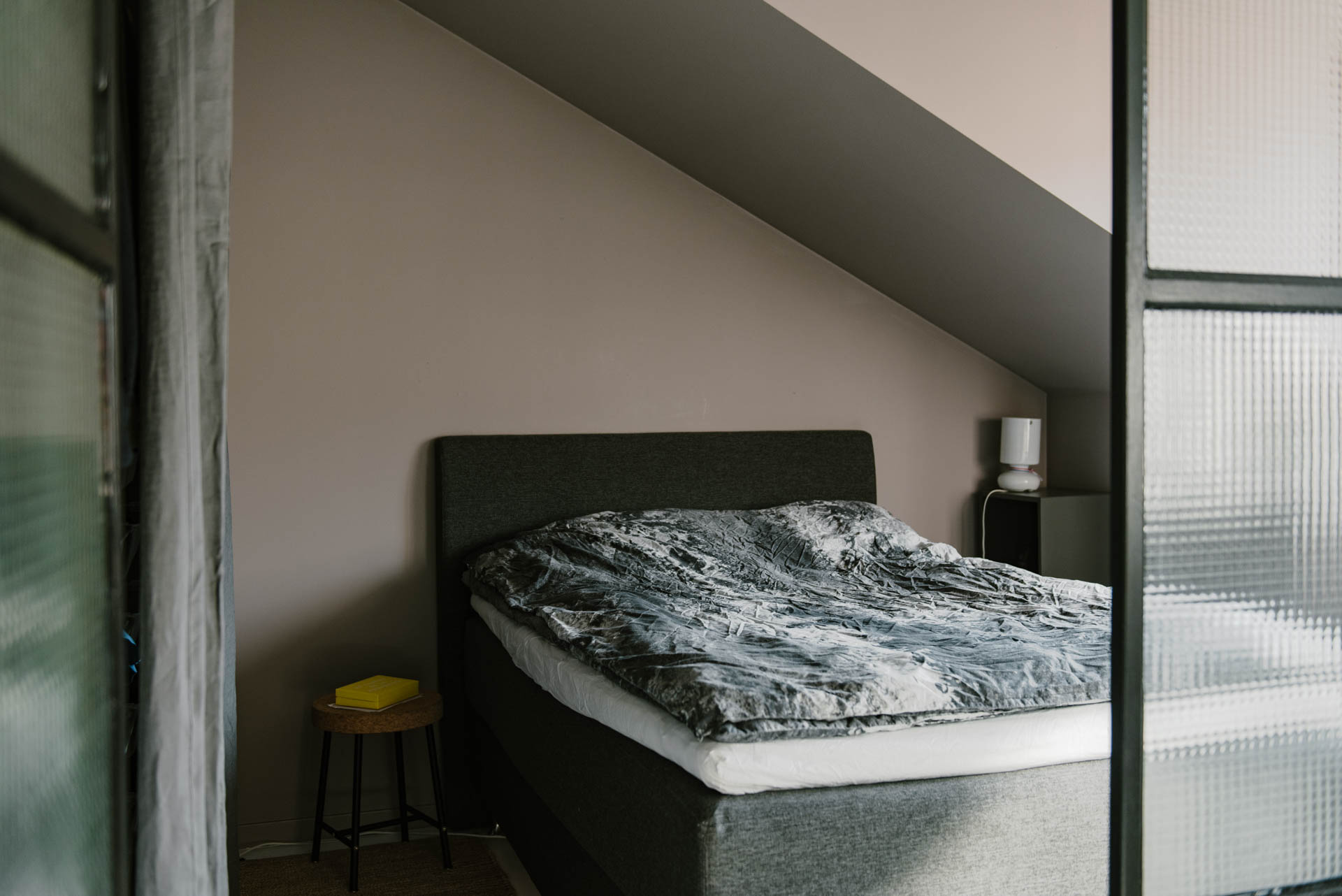 deze kleine slaapkamer met schuine wand is erg stoer ingericht