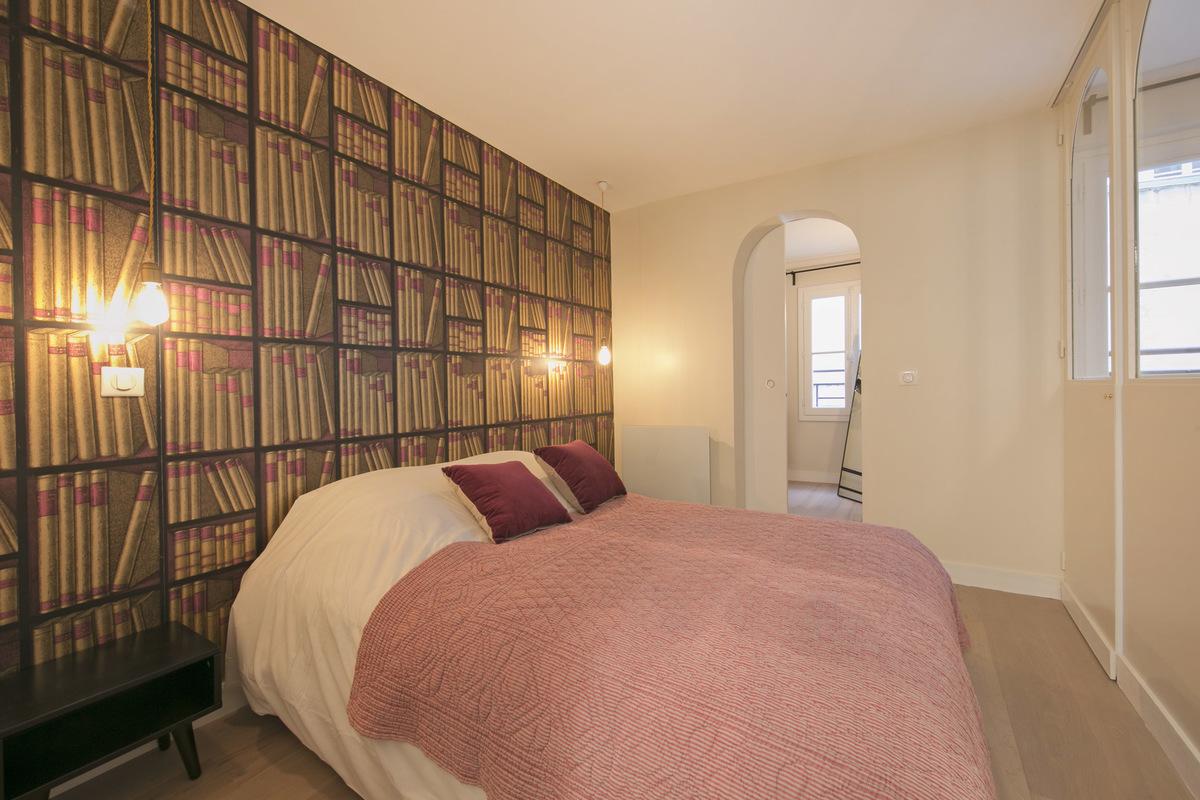 Deze slaapkamer is gedecoreerd met mooie boekenkast behang!