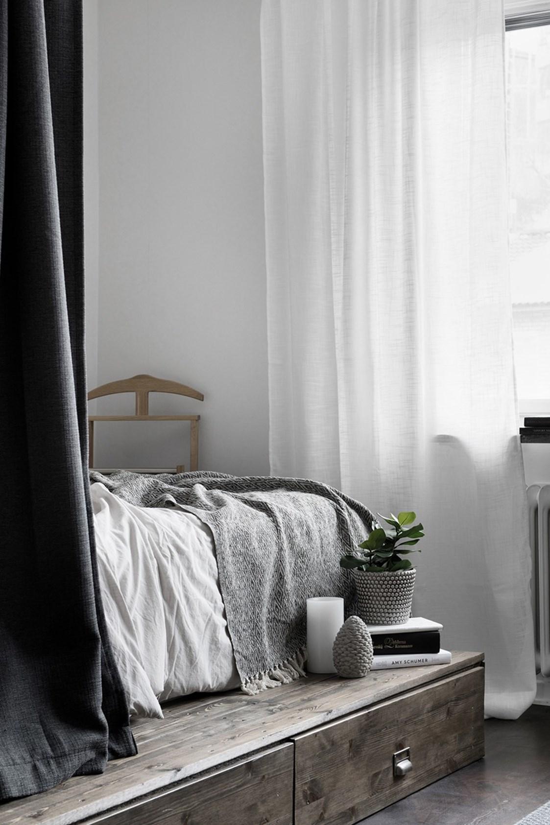 Kleine slaapkamer met een houten platform met ladekasten