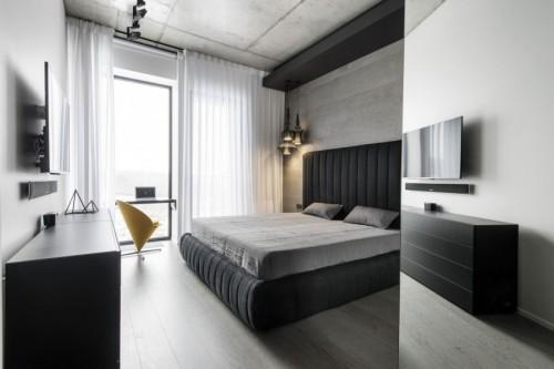 Moderne slaapkamer met een betonnen plafond