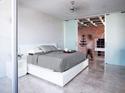 Moderne slaapkamer met hoogglans betonnen vloer