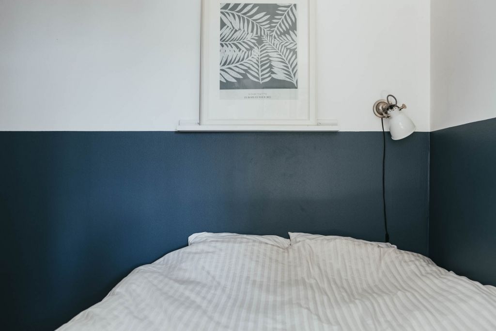 Mooie minimalistische slaapkamer met geverfde blauw lambrisering ...