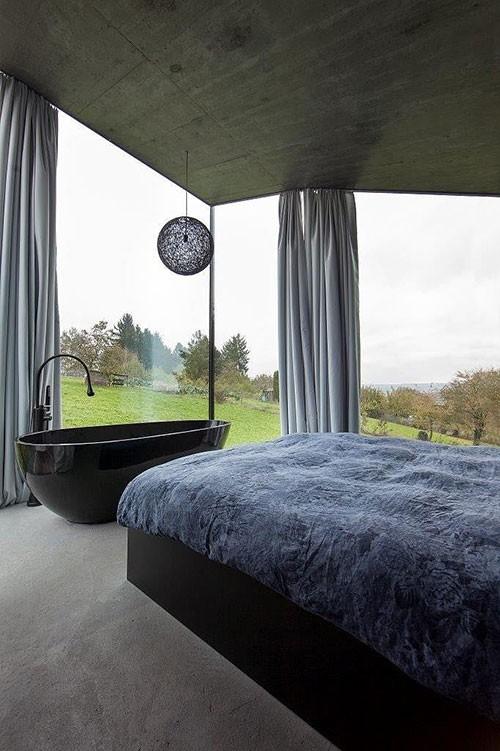 Slaapkamer met glazen buitenmuren en uitzicht