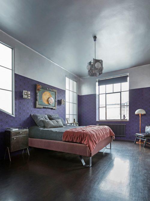 Slaapkamer met paarse muren van een voormalige wapenfabriek