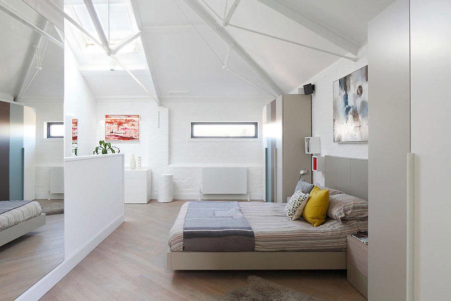 Stoere zolderslaapkamer met wit geschilderde bakstenen muren