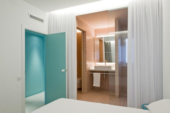 Strakke minimalistische slaapkamer met een half open roze badkamer ...